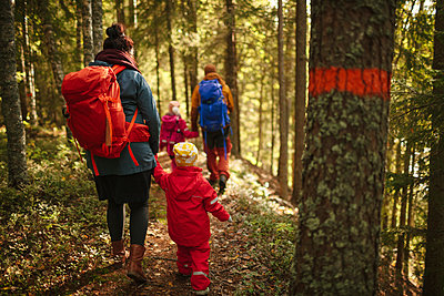Family walking through forest - p312m2190371 by Matilda Holmqvist