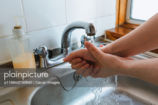 Young woman Is Cleaning Her Hands - p1166m2190840 by Cavan Images