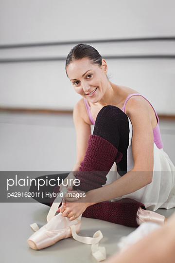 Ballet dancer tying her shoe in studio