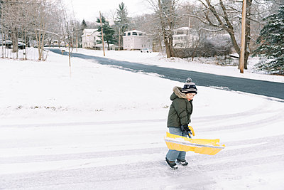 Little boy shoveling the snow in his driveway and helping his parents. - p1166m2152181 by Cavan Images