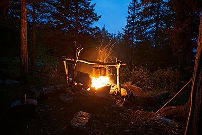 Containers hanging over fire at campsite - p1166m968464f by Cavan Images
