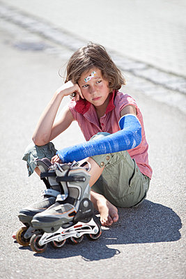 Germany, Bavaria, Wounded girl sitting on road after inline-skating accident - p30019971f by Roman Märzinger