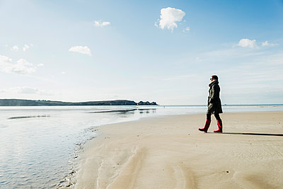 France, Bretagne, Finistere, Crozon peninsula, woman walking on the beach - p300m1120855f by Uwe Umstätter