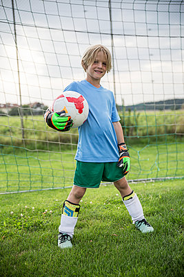 Portrait of smiling young football goalkeeper holding ball on football ground - p300m1581031 by Fotoagentur WESTEND61