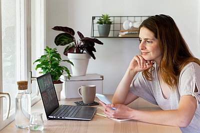 Smiling female professional doing video call on laptop at home office - p300m2287113 by VITTA GALLERY