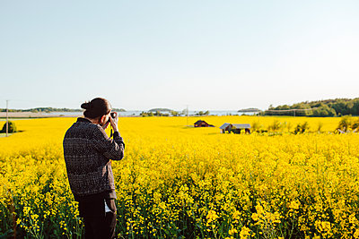 A young man taking a photograph of a country scene - p352m1523650 by Benjamin Rudström