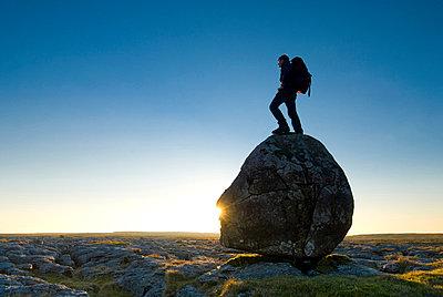 Hiker standing on head-shaped boulder - p6441366 by Ian Cumming