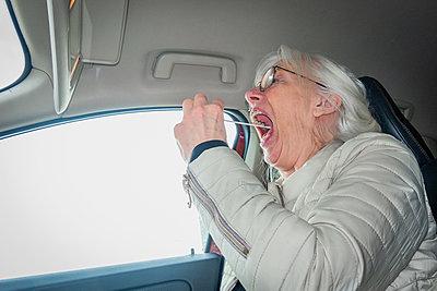 Woman taking drive-in test for covid-19 - p1418m2257909 by Jan Håkan Dahlström