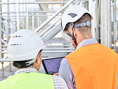 Architect and foreman with tablet wearing hards hat on construction site - p300m1588021 von Christian Vorhofer