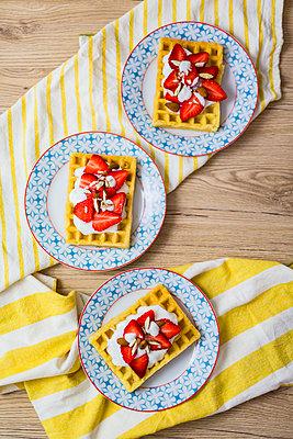 Three plates of waffles garnished with strawberries, Greek yogurt and almonds - p300m2005605 von Giorgio Fochesato
