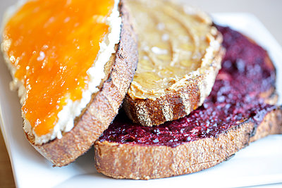 Sliced bread with jam, cheese, and nut butter - p343m1569184 by Clay McLachlan