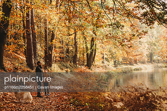 Boy and father standing under trees next to canal in fall - p1166m2258451 by Cavan Images