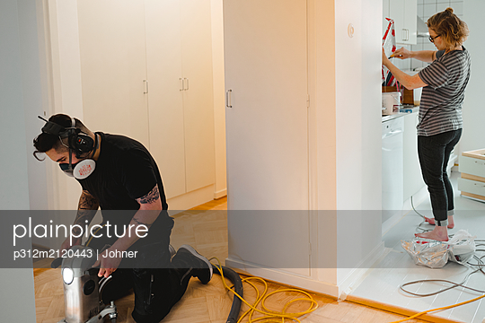 Man and woman renovating apartment - p312m2120443 by Johner