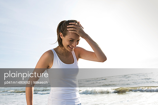 Young woman on St. Peter-Ording beach - p341m1480692 by Mikesch