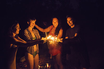 Friends playing with sparklers at night - p1166m1174268 by Cavan Images