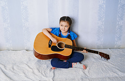Cute girl with braid playing guitar at home - p1577m2263978 by zhenikeyev