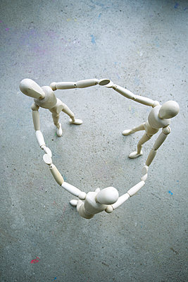 Three wooden manikins holding hands on grey ground - p300m977888f by Mandy Reschke