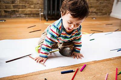 Male toddler sitting on floor drawing on long paper - p429m1418480 by Bonfanti Diego