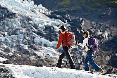 Mother and daughter walking on glacier - p429m726997f by Henn Photography