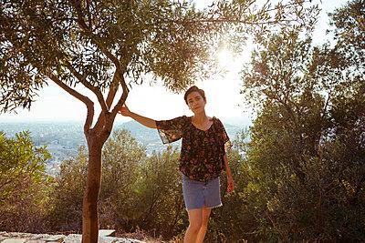 Zufriedene Frau lehnt sich an Baum - p432m1510999 von mia takahara