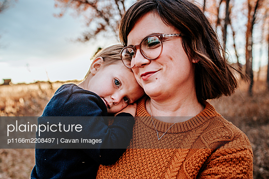Content toddler hugging his smiling mom outside on an autumn evening - p1166m2208497 by Cavan Images