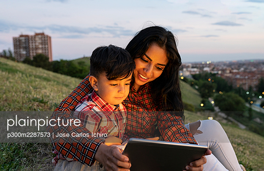 Smiling mother and son using digital tablet while sitting on hill - p300m2287573 by Jose Carlos Ichiro