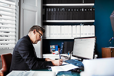 A man sitting at a desk in an office, writing on a piece of paper. Neat rows of files on shelves and papers on the desk.  - p1100m1177696 by Mint Images