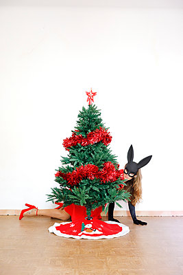 Woman with rabbit ears behind christmas tree, portrait - p1105m2215089 by Virginie Plauchut