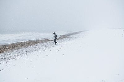 Man going surfing during winter snow - p1166m2177100 by Cavan Images