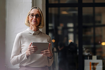 Portrait of mature businesswoman holding tablet in office - p300m2156087 by Gustafsson