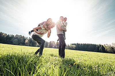 Happy family with two kids on a meadow in spring - p300m2167626 by Wilfried Feder