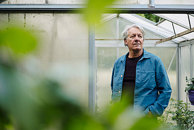 Portrait of a senior man standing at a greenhouse - p300m2202705 by Gustafsson