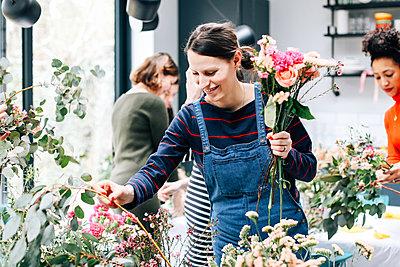 Florist student selecting cut flowers at flower arranging workshop - p429m1418094 by Alys Tomlinson
