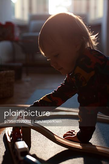 Kleinkind spielt mit Holzeisenbahn - p795m2229302 von JanJasperKlein