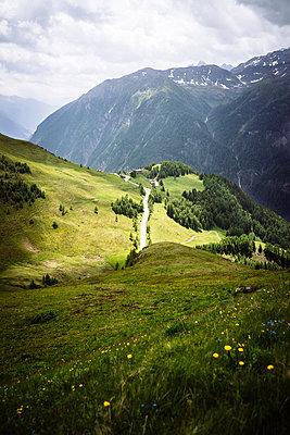 Winding road on alpine landscape - p1053m1122634 by Joern Rynio