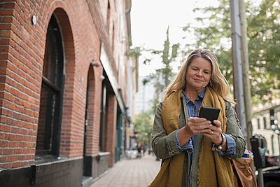 Mature woman texting with smart phone on urban sidewalk - p1192m1512055 by Hero Images