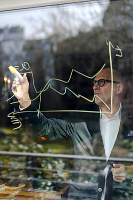senior businessman brainstorming, drawing formulas on window pane - p300m1587926 von Gustafsson