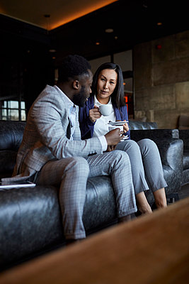 Businessman and businesswoman sitting on couch in hotel lobby having a coffee break - p300m2171396 by Zeljko Dangubic