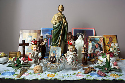 Religious statues and prayer symbols on a table - p5350198 by Michelle Gibson