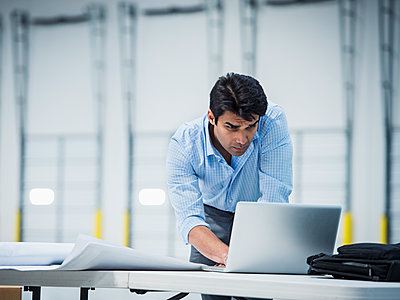 Indian architect using laptop in empty warehouse - p555m1305147 by Erik Isakson