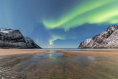 Sandy beach and snowy peaks framed by the Northern Lights (aurora borealis) in the polar night, Ersfjord, Senja, Troms, Norway, Scandinavia, Europe - p871m1478711 by Roberto Moiola