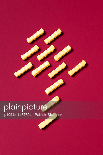 High angle view of French fries toys arranged on red background - p1094m1467624 by Patrick Strattner