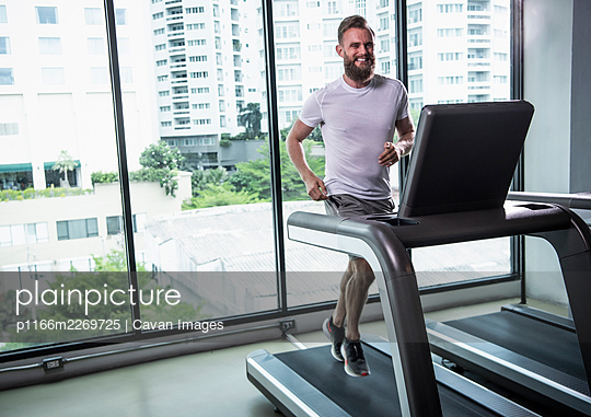 man with beard running on treadmill at gym in Bangkok - p1166m2269725 by Cavan Images