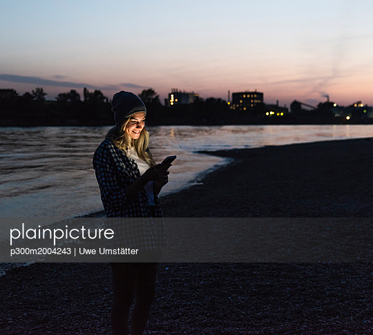 Young woman using smartphone on riverside in the evening - p300m2004243 von Uwe Umstätter
