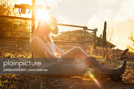 Woman sitting on a farm at sunset - p300m2005263 von zerocreatives