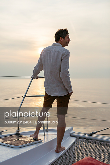 Marure man on catamaran, looking ta view - p300m2012484 von Bonninstudio