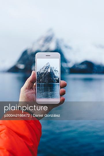 Close-up of tourist taking a smartphone picture at Hamnoy, Lofoten, Norway - p300m2166472 von Daniel González