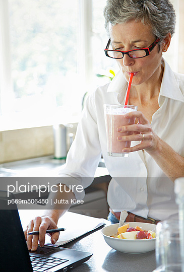 Woman Drinking Smoothie whilst Typing on Laptop - p669m806480 by Jutta Klee photography