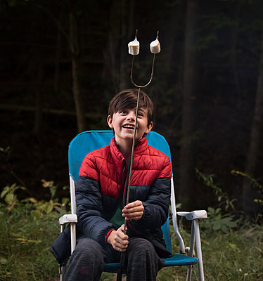 Happy boy looking at roasted marshmallows on a metal stick. - p1166m2214643 by Cavan Images