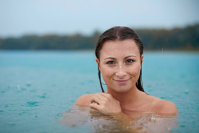 Portrait of smiling young woman  bathing in lake on rainy day - p300m2042874 von Philipp Nemenz